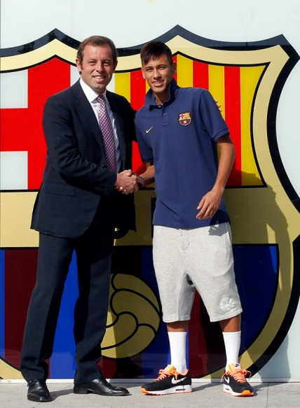 Neymar shakes hands with Barcelona's president Sandor Rosell after signing his contract with FC Barcelona, in front of their offices close to Camp Nou stadium in Barcelona